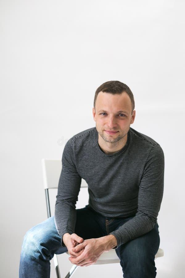 O homem europeu novo está sentando-se na cadeira branca fotografia de stock royalty free