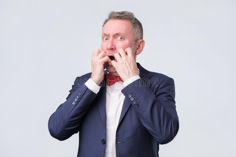 O homem europeu superior morde pregos do dedo no esforço foto de stock