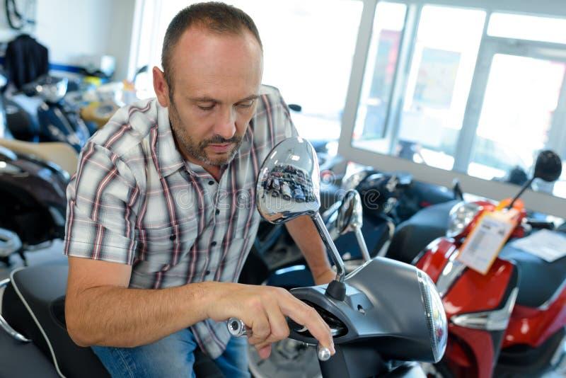 O homem examina a motocicleta na loja imagem de stock royalty free