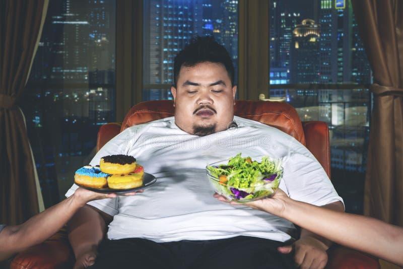 O homem excesso de peso confundido escolhe o alimento fotografia de stock