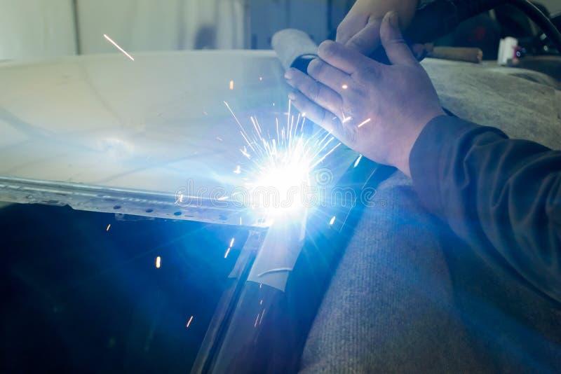 O homem experiente executa o trabalho no carro do reparo do corpo com uma máquina de soldadura fotos de stock
