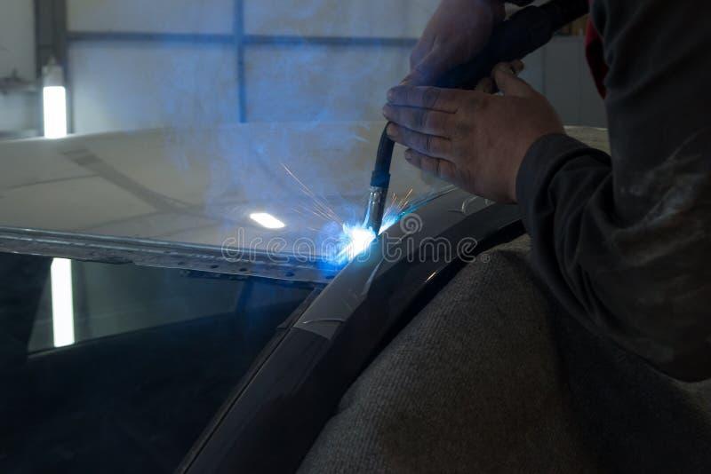 O homem experiente executa o trabalho no carro do reparo do corpo com uma máquina de soldadura foto de stock