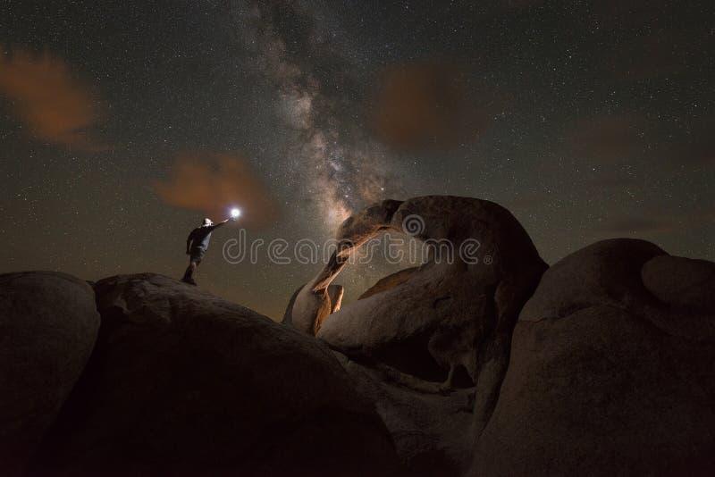 O homem explora o arco de Mobius sob o céu noturno imagens de stock