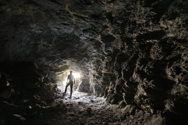 O homem explora uma caverna foto de stock