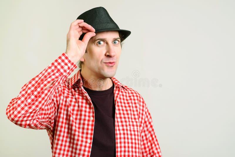 O homem eyed azul mantém a mão no chapéu e a vista à câmera Homem engraçado com as emoções positivas, levantando sobre a parede c foto de stock royalty free