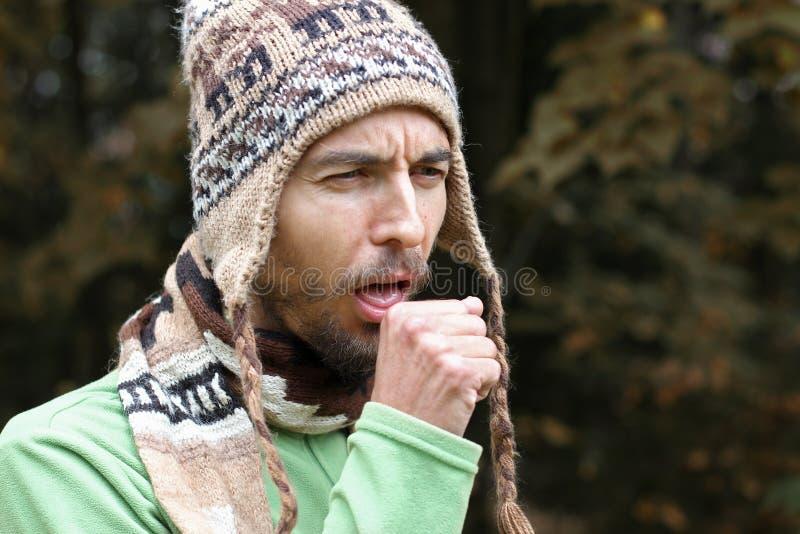 O homem farpado adulto em um chapéu e em um lenço mornos tosse no outono s fotografia de stock
