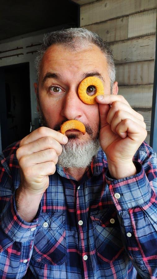 O homem farpado adulto feliz guarda duas cookies na forma de uma filhós e um mês na frente de sua cara, descreve um monóculo e um imagem de stock royalty free