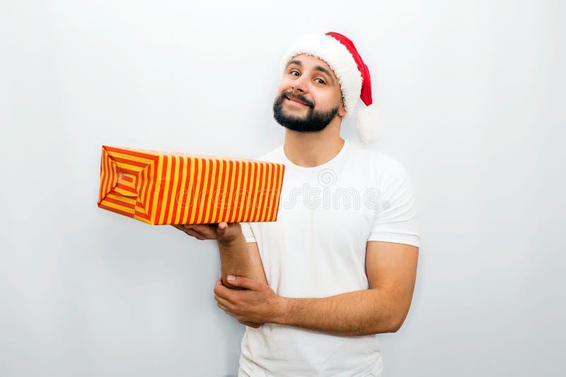 O homem farpado agradável no chapéu vermelho está e guarda a caixa alaranjada com presente em uma mão Olha na câmera e sorri um b fotografia de stock