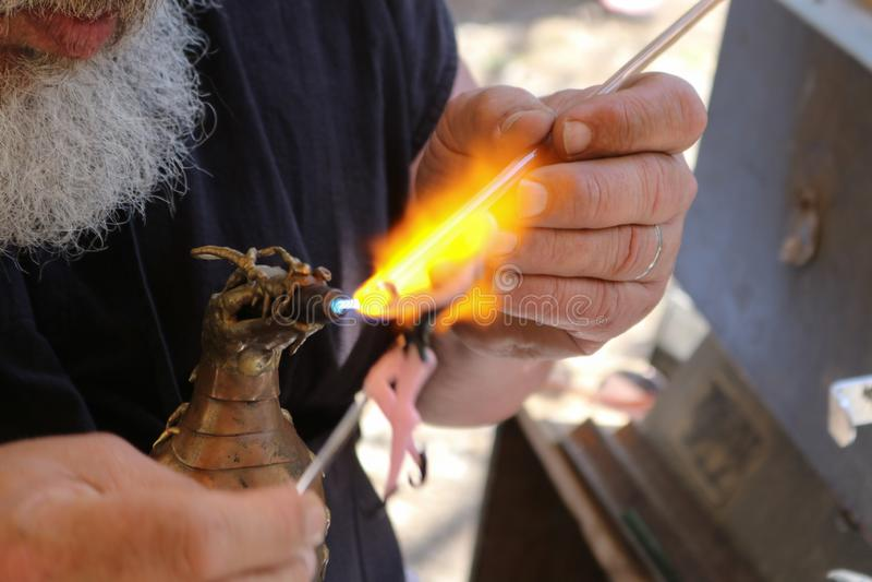 O homem farpado branco colhido cria a fada de vidro que usa lampworking - as hastes de vidro de derretimento com uma tocha abaste fotografia de stock