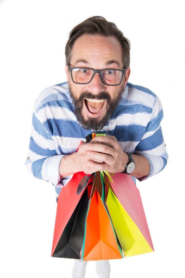 O homem farpado com vidros guarda o grupo dos sacos de compras Homem com a cara surpreendida louca com sacos de compras Conceito  fotos de stock royalty free