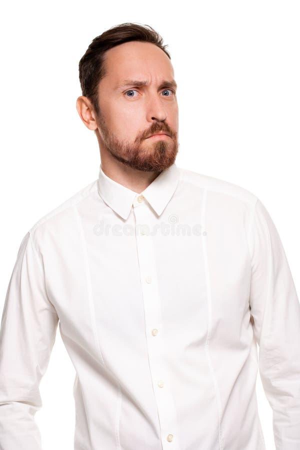 O homem farpado considerável em uma camisa branca levanta, isolado em um fundo branco fotografia de stock