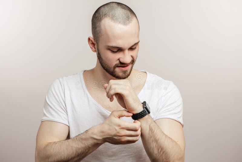 O homem farpado considerável está tocando em seu relógio imagens de stock royalty free