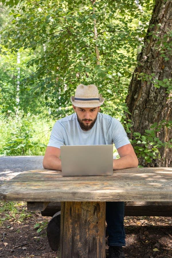 O homem farpado das pessoas de 23 anos novas olha a tela do portátil As buscas para uma amiga no Internet, olham um local datando imagem de stock royalty free