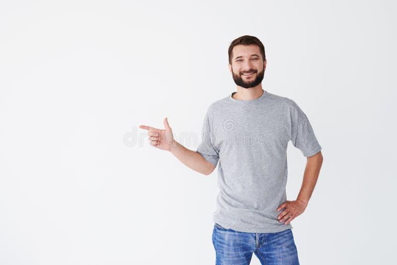 O homem farpado de sorriso que aponta à cópia espaça dentro imagens de stock