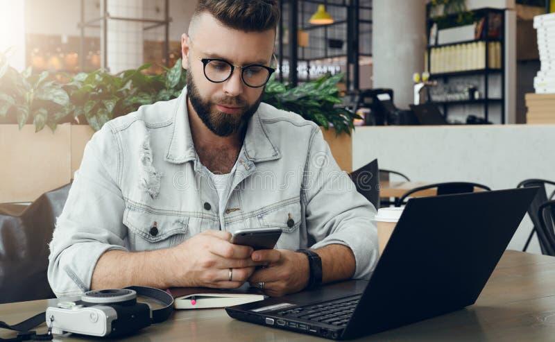O homem farpado do moderno nos vidros senta-se no café na tabela, trabalhos no portátil, smartphone dos usos Na tabela é o cadern fotos de stock royalty free