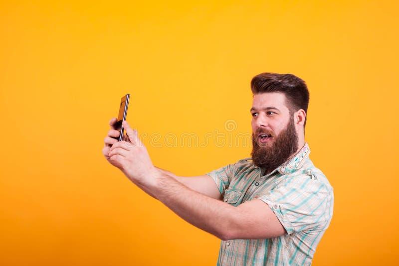 O homem farpado do moderno que tem um vídeo chama seu telefone sobre o fundo amarelo foto de stock