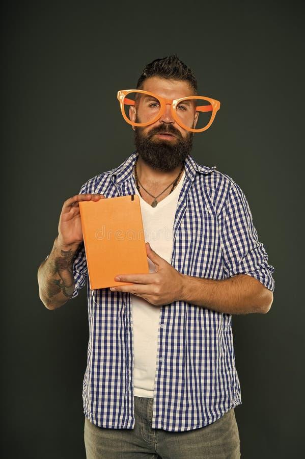 O homem farpado do moderno veste mon?culos engra?ados guarda o bloco de notas ou o livro Ascendente brilhante seu dia Leia este l foto de stock