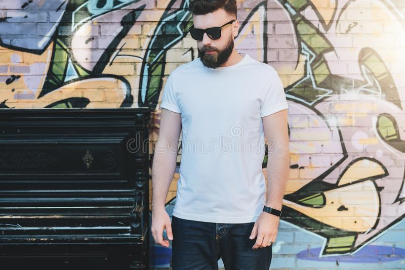 O homem farpado do moderno vestido no t-shirt branco é suportes contra a parede com grafittis Zombaria acima Espaço para o logoti imagens de stock royalty free