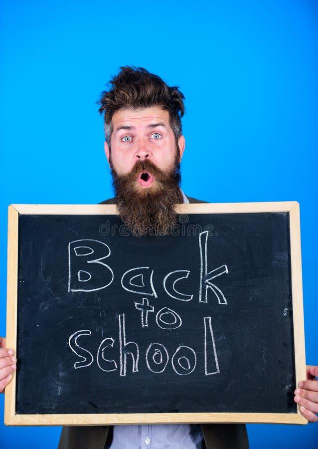 O homem farpado do professor está e guarda o quadro-negro com inscrição de volta ao fundo do azul da escola Continue sua educação fotografia de stock