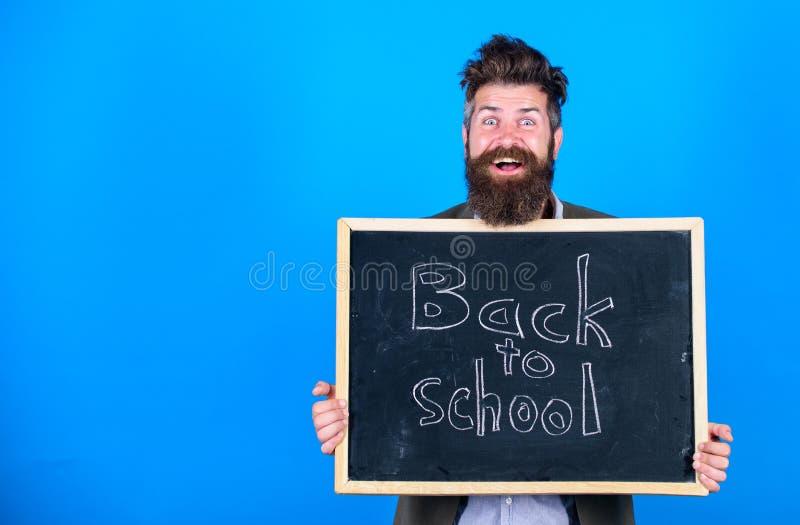 O homem farpado do professor está e guarda o quadro-negro com inscrição de volta ao fundo do azul da escola O professor convida a fotos de stock royalty free