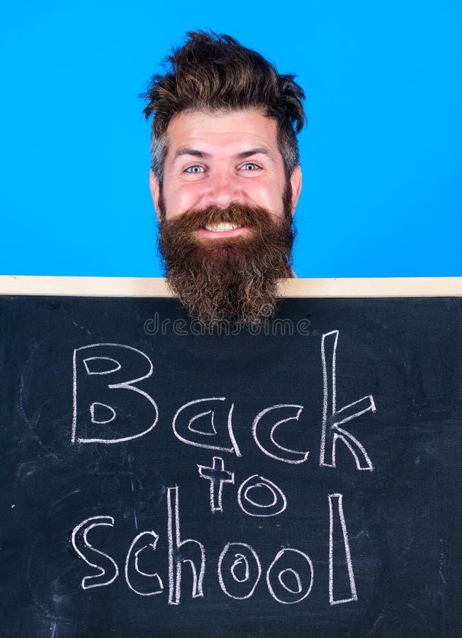 O homem farpado do professor está e guarda o quadro-negro com inscrição de volta ao fundo do azul da escola O professor convida a imagens de stock royalty free
