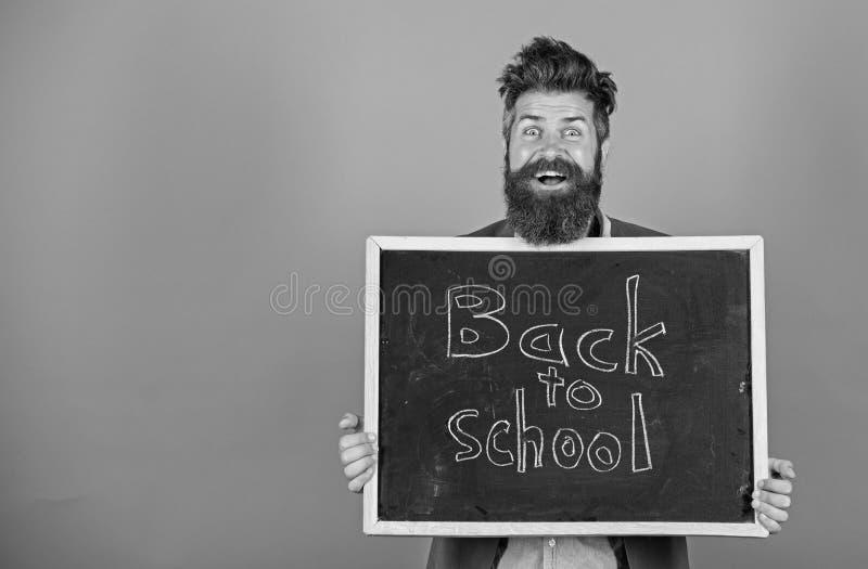O homem farpado do professor está e guarda o quadro-negro com inscrição de volta ao fundo do azul da escola O professor convida a fotografia de stock