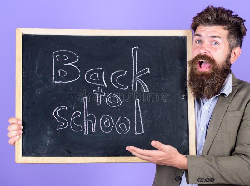O homem farpado do professor está e guarda o quadro-negro com inscrição de volta ao fundo da violeta da escola O professor convid imagens de stock