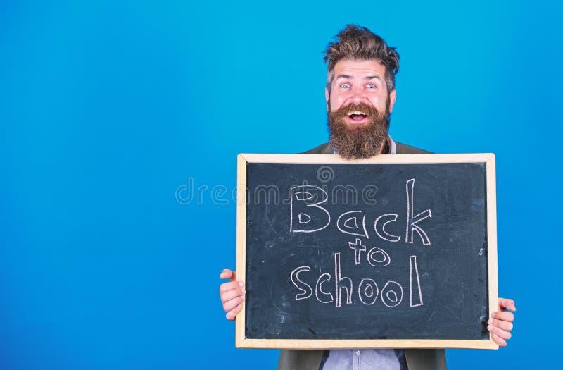 O homem farpado do professor est? e guarda o quadro-negro com inscri??o de volta ao fundo do azul da escola O professor convida a foto de stock