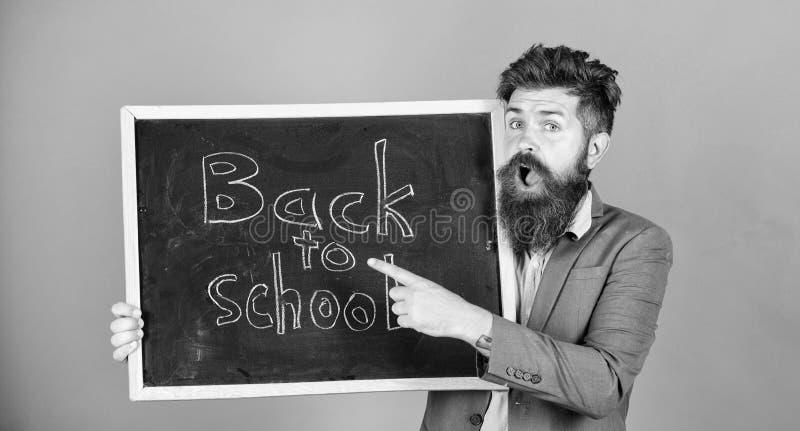 O homem farpado do professor est? e guarda o quadro-negro com inscri??o de volta ao fundo da violeta da escola Continue o seu imagem de stock