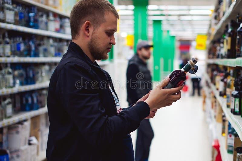 o homem farpado, em um revestimento preto, parado para fazer minha escolha na janela de loja, guarda uma garrafa do álcool forte foto de stock