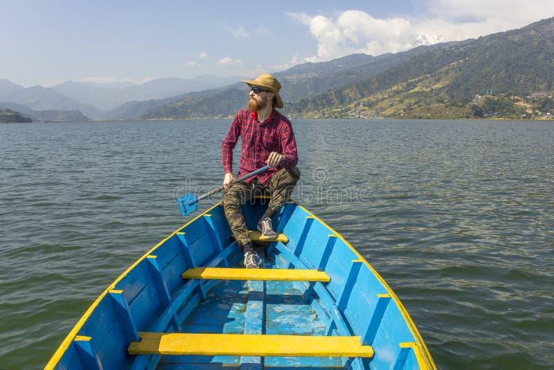 o homem farpado em uma camisa, em um chap?u e em uns ?culos de sol vermelhos est? sentando-se em um barco azul com uma p? no lago fotografia de stock