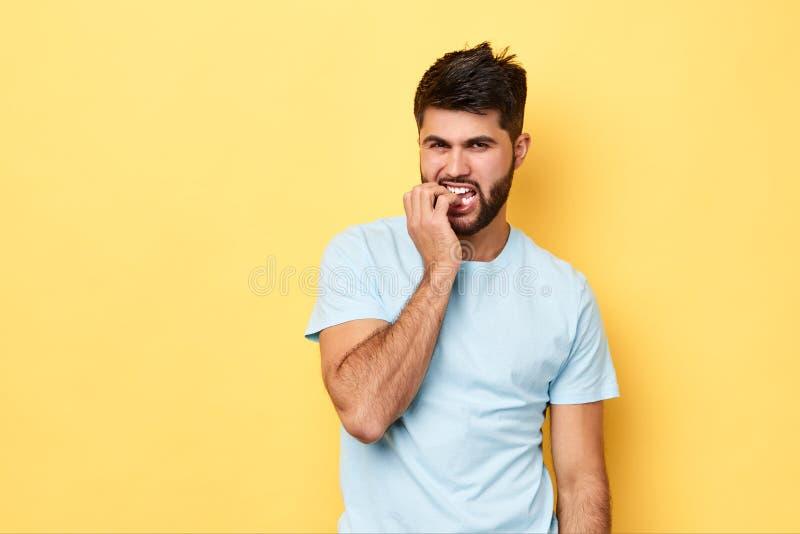 O homem farpado embaraçado nervoso morde os pregos, olhares preocupados antes dos exames fotografia de stock