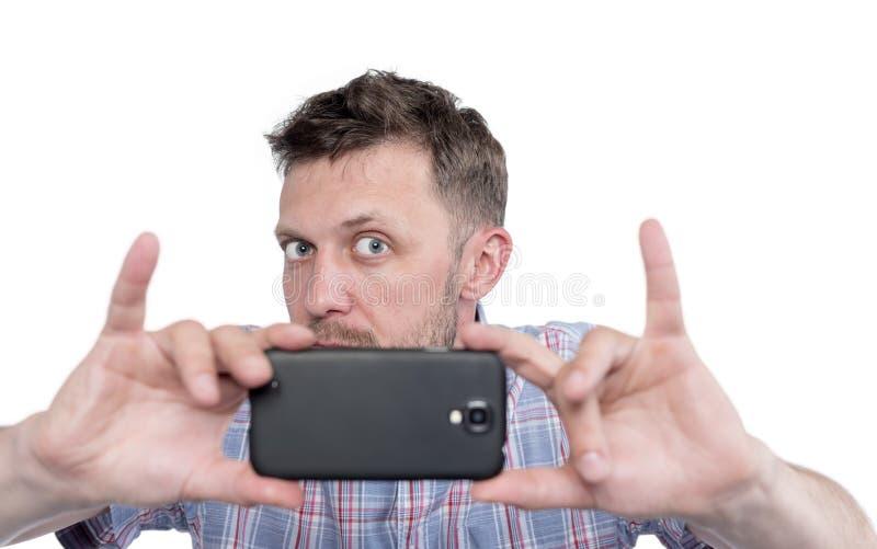 O homem farpado fotografou pelo smartphone, isolado no fundo branco imagens de stock royalty free