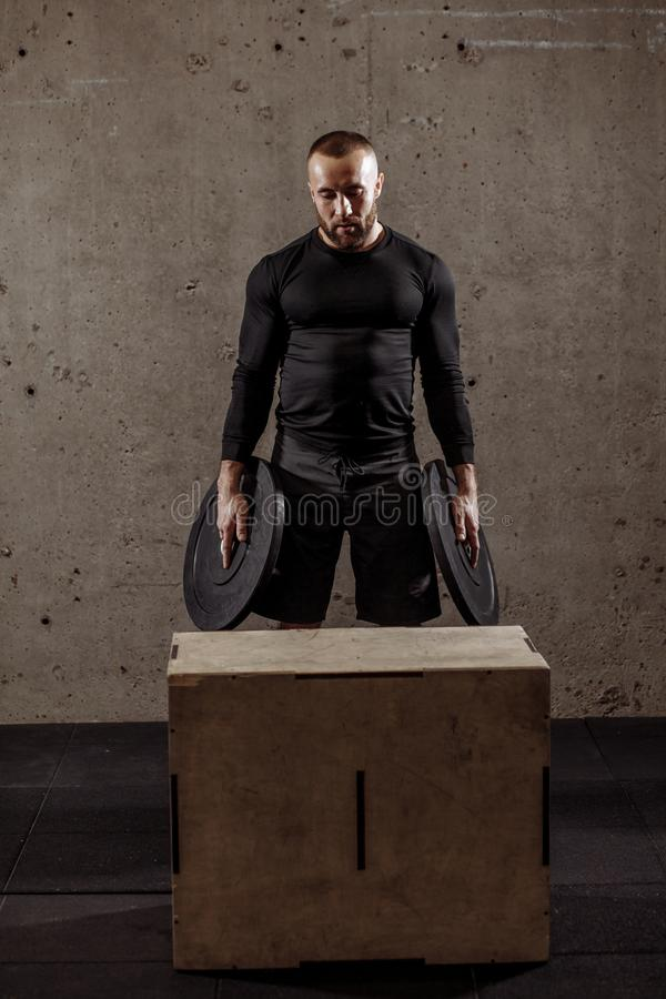 O homem farpado lindo novo do ajuste com placa do peso está estando na frente da caixa fotos de stock