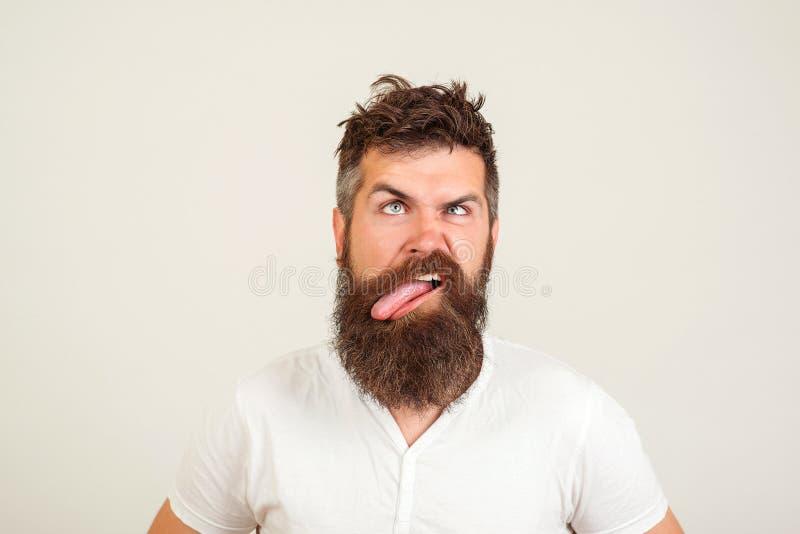 O homem farpado louco mostra sua língua, no fundo branco Expressão negativa da cara, emoção humana, linguagem corporal, reação Br foto de stock