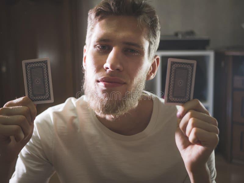 O homem farpado novo em cartões guardando ocasionais do playng mostra o retrato de alguns truques em casa fotografia de stock