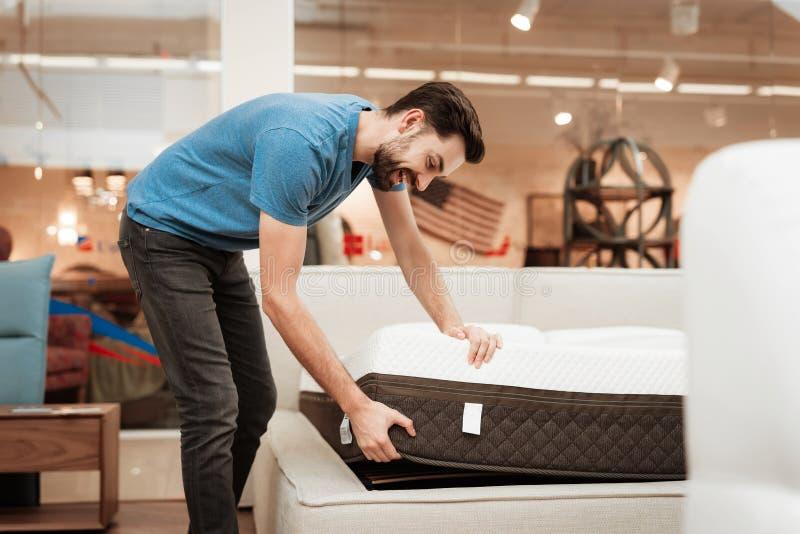 O homem farpado novo está testando o colchão na loja da mobília Colchão ortopédico para uma postura saudável fotos de stock