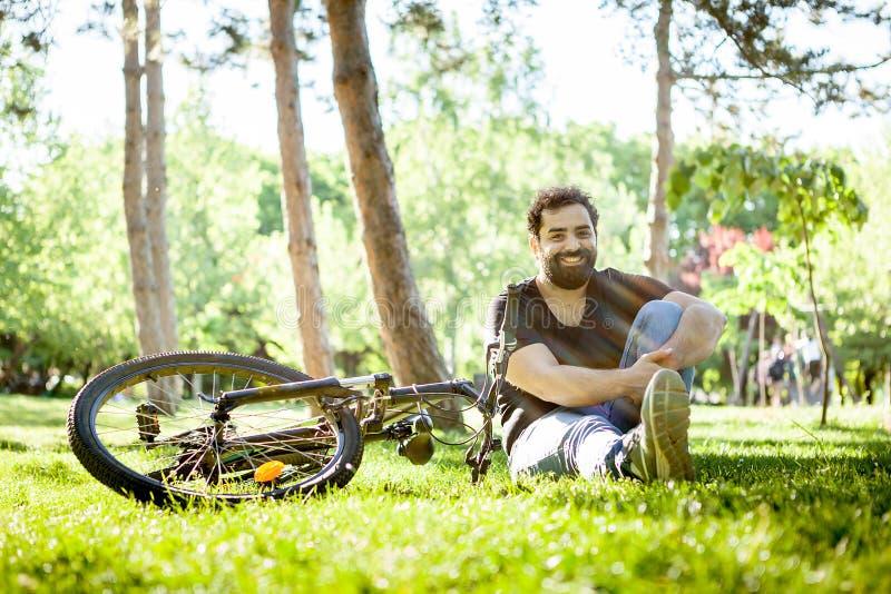 O homem farpado novo sorri à câmera que senta-se na terra na grama fotografia de stock