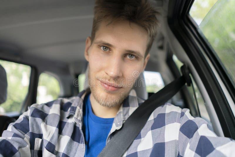 O homem farpado novo toma um autorretrato dsi mesmo que senta-se nos bancos de carro dianteiros fotografia de stock royalty free