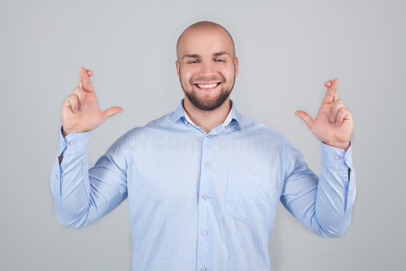O homem farpado positivo contente cruza os dedos, fecha os olhos com prazer, antecipa a boa notícia da audição, fundo branco imagens de stock royalty free