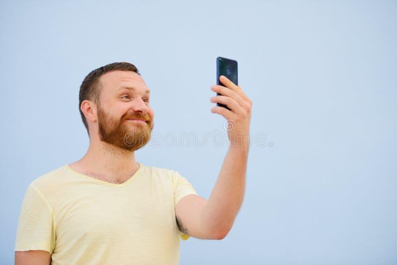 O homem farpado que olha no telefone exulta a foto para anunciar muito espaço sob o texto fotografia de stock