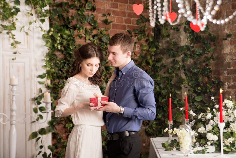O homem faz o presente, caixa para sua amiga Valentim, amor e relacionamento Ternura imagem de stock