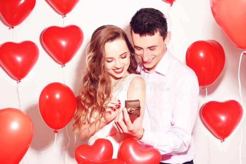 O homem faz o presente a sua menina bonita do querido O dia de são valentim do amante Valentine Couple O menino dá a sua joia da  imagens de stock royalty free