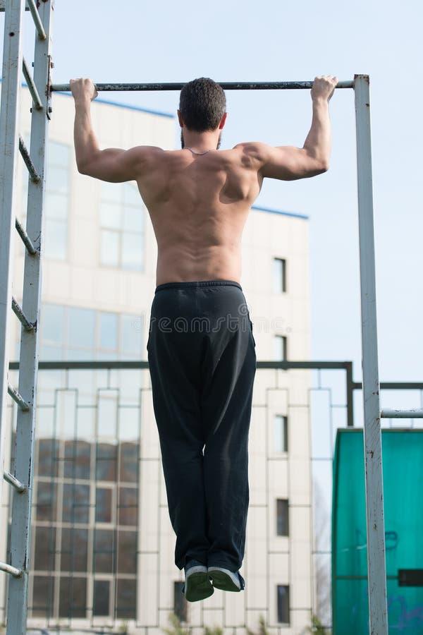 O homem faz o queixo levanta exterior O desportista levanta no estádio Atleta com torso do ajuste e mãos fortes na barra Chin aci foto de stock royalty free