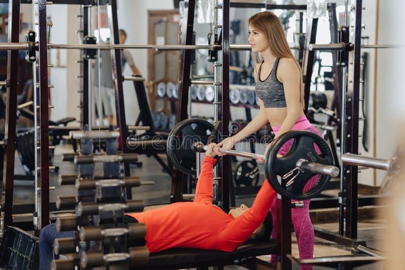 O homem faz uma imprensa de banco, ele é segurado por um treinador da menina, um tema do gym dos esportes imagens de stock
