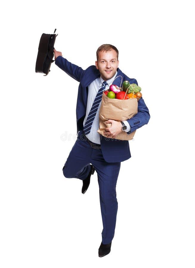 O homem feliz corre com o saco saudável do alimento, comprador do mantimento isolado imagem de stock