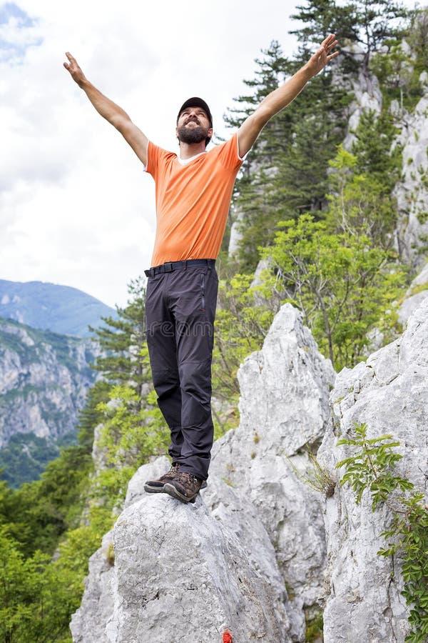 O homem feliz do caminhante que comemora na parte superior da montanha com braços levanta o imagens de stock royalty free