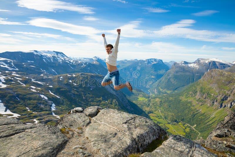 O homem feliz do turista sobre Geirangerfjord e as montanhas ajardinam do ponto de vista de Dalsnibba, Noruega fotos de stock