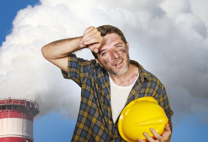 O homem feliz e cansado atrativo do contratante ou do trabalhador da construção que guarda o capacete e a sujeira de segurança ma fotografia de stock royalty free