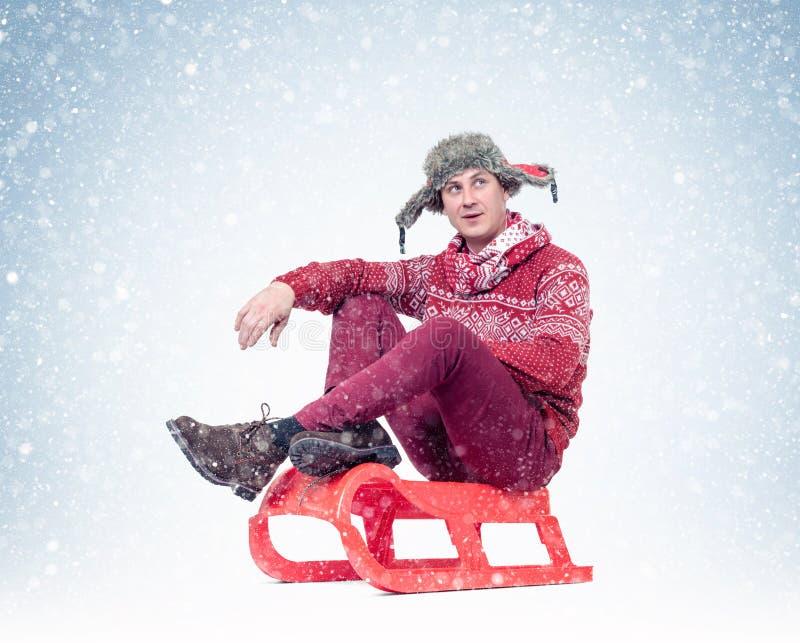 O homem feliz em uma camiseta, em um lenço e em um chapéu vermelhos está sentando-se em um trenó que olha a neve de queda imagem de stock